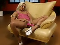 Hot babe fucks her pussy on a couch